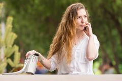 Young girl with a handbag talking on phone stock photos