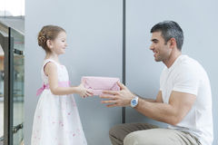 Young girl handing present to her father Royalty Free Stock Photos