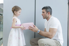 Young girl handing present to her father Royalty Free Stock Image