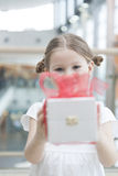Young girl handing present towards camera Stock Photography