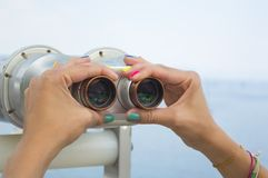 Young girl hands with painted nails holding public binoculars wi Royalty Free Stock Photos