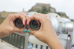 Young girl hands with painted nails holding public binoculars wi Stock Photo