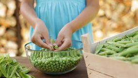 Young girl hands shelling peas and stirring the beans in a glass bowl stock video