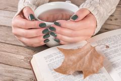 Woman hands in sweater with olive color manicure holds cup of tea and open book. Young girl hands in sweater with olive color manicure holds cup of tea and open stock photo