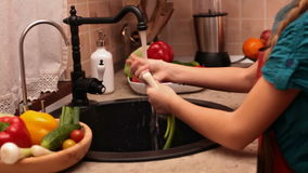 Young girl hands washing vegetables at the kitchen sink. Rinsing some spring onions, camera sliding and tracking the hands