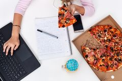 Young girl hands working at the desk while eating pizza