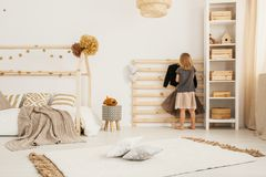 Young girl hanging clothes on wooden hanger in white Nordic style bedroom interior with home-shape bed, two pillows placed on car. Young girl hanging clothes on stock image