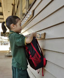Young Girl Hanging Up Her School Bag. Royalty Free Stock Image