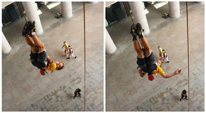 Young girl hanging upside down. From a rope after she climb an artificial wall. Location: Iulius Mall Timisoara, Romania. Summer 2011 Stock Image