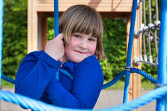 Young girl hanging in web of blue ropes Stock Photography