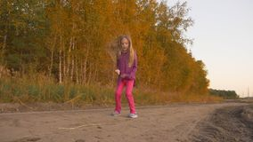 Young girl happy jumping outdoors. Dancing hip-hop near golden forest autumn sunset. Slow motion. stock video footage