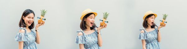 Young girl happy smile and cheerful in blue dress, hold two pineapple in hand. royalty free stock image