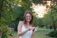 Young girl has a great mood. Beautiful woman is listening to her favourite song in headphones on mobile phone. Smiling and. Laughing lady is dancing in the park royalty free stock photography