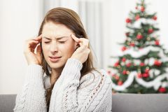Young girl has headache of christmas stress Royalty Free Stock Images
