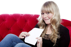 Young girl has a romance and got a letter. Young blond haired girl has a romance and got a letter on red sofa in front of white background Royalty Free Stock Photo