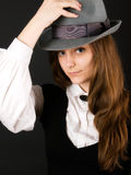 Young girl in hat. Pretty young girl keeps one's hat in dark colours Stock Image