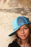 Young girl with hat with back against the wall. A pretty teenage girl smiling towards the camera with her back against a stone wall. With attitude but still Royalty Free Stock Photography