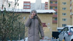 Young girl in hat and coat eating ice cream on winter walk in snowy city. Cheerful girl teenager walking in winter city stock footage