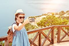 Young girl in a hat and dress with a backpack royalty free stock image