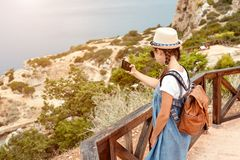 Young girl in a hat and dress with a backpack stock photography