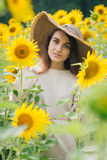 Young girl in a hat on a field of sunflowers Royalty Free Stock Photos
