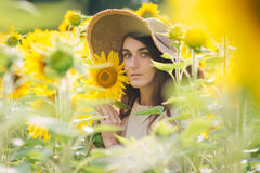 Young girl in a hat on a field of sunflowers Stock Photo