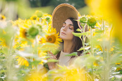 Young girl in a hat on a field of sunflowers Stock Images