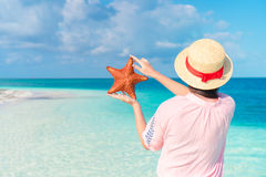 Young girl in hat holding giant red starfish on white beach in the nature reserve Stock Photography