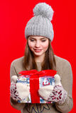 Young girl in hat and mittens with gift box Stock Photo