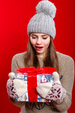 Young girl in hat and mittens with gift box Stock Images