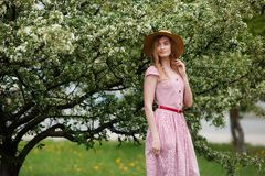 Young girl in a hat near a flowering tree in the park. Pretty tenderness model looking at camera stock image