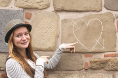 Young girl in the hat near the wall with drawn chalk heart. Royalty Free Stock Photo