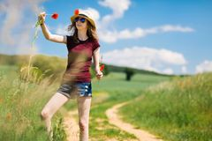 A young girl in hat is plucking a poppy flowers - by the cart road stock photo