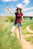 A young girl in hat rip out poppy flower with roots stock photo