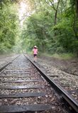 Girl in hat walking down fog covered railroad tracks royalty free stock photography