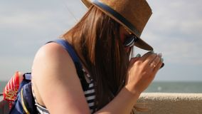 Young girl in a hat walks at promenade in summer, keep a telephone and plans takes a photo on her smartphone, enjoys a. Walk stock footage