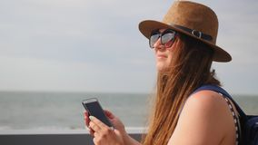 Young girl in a hat walks at promenade in summer, keep a telephone and plans takes a photo on her smartphone, enjoys a. Walk stock video