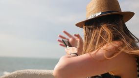 Young girl in a hat walks at promenade in summer, keep a telephone and plans takes a photo on her smartphone, enjoys a. Walk stock video footage