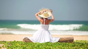 Young girl in hat and white dress sitting on the beach stock video