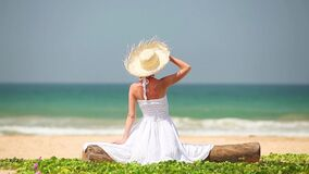 Young girl in hat and white dress sitting on the beach stock footage