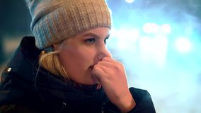 A young girl in a hat in winter stands at the traffic lights, she blows her nose. Against the background of the night lights of passing cars in the city stock video