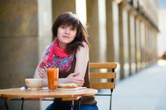 Young girl having breakfast in a cafe Stock Images