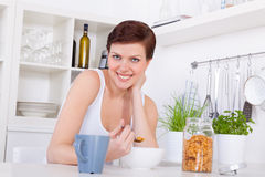 Young girl having breakfast with cornflakes and tea in her kitch Stock Images