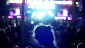 Young girl having fun dancing at a rock concert on the background of the scene with colored lights
