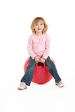 Young Girl Having Fun On Inflatable Hopper. Studio Portait of Young Girl Having Fun On Inflatable Hopper stock images