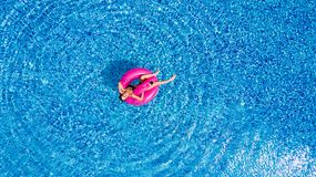 Young girl having fun and laughing and having fun in the pool on an inflatable pink flamingo in a bathing suit in summer from abov royalty free stock image