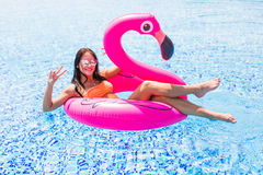 Young girl having fun and laughing on an inflatable giant pink flamingo pool float mattress in a bikini. Attractive tanned woman l Royalty Free Stock Photography