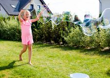 Girl making soap bubbles in home garden royalty free stock images