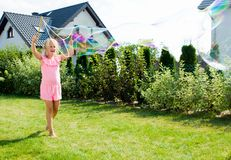 Girl making soap bubbles in home garden stock photography