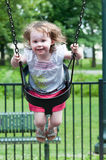 Young girl having fun outside at park on a playground swing set Royalty Free Stock Photography